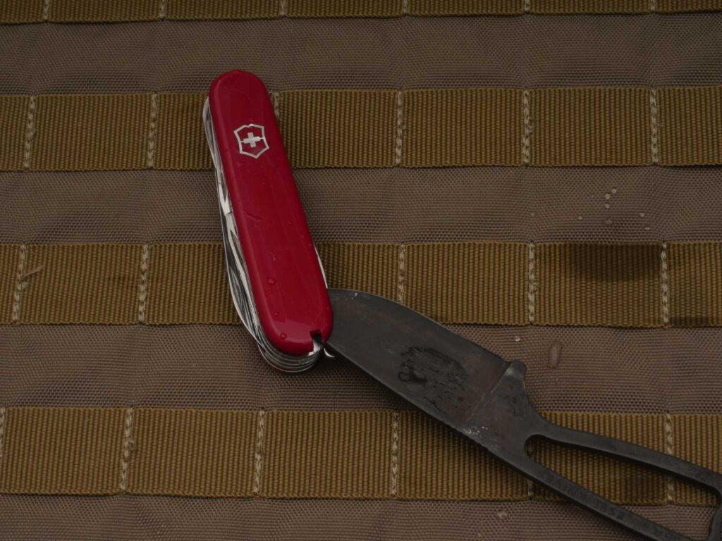 Entnehme das SAK aus dem Wasser und bringe die Messerklinge vorsichtig zwischen Griffschale und Metallplatine